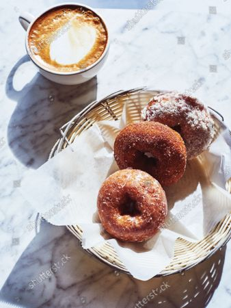 Cappuccino and doughnuts on a marble countertop.