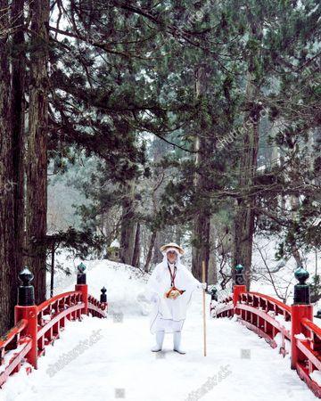 A Yamabushi monk on the Shinkyo Bridge in the forest, in Japan.