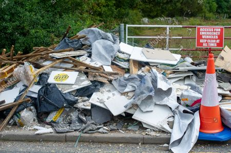 Stock Image of Building material fly tipped on a country lane next to an emergency access point. There has been a huge increase in illegal fly tipping in Buckinghamshire. Buckinghamshire Council now make charges for the disposal of some household items ranging from £3.10 to £24.80 per item which may be the reason why illegal fly tipping has increased so much in Buckinghamshire