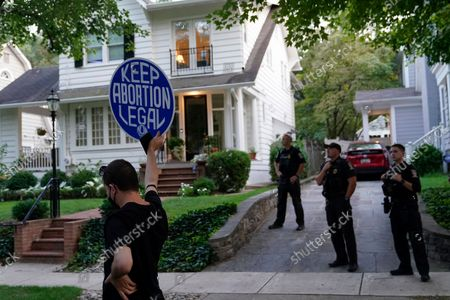Protester stands outside the home of Supreme Court Justice Brett Kavanaugh, in Chevy Chase, Md., after a high-profile decision earlier this month in which the court by 5-4 vote declined to step in to stop a Texas law banning most abortions from going into effect, prompting outrage from abortion rights groups and President Joe Biden