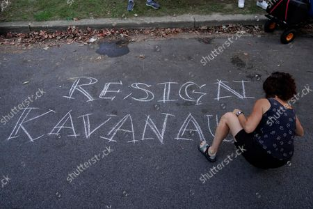 Protester writes in chalk outside the home of Supreme Court Justice Brett Kavanaugh, in Chevy Chase, Md., after a high-profile decision earlier this month in which the court by 5-4 vote declined to step in to stop a Texas law banning most abortions from going into effect, prompting outrage from abortion rights groups and President Joe Biden