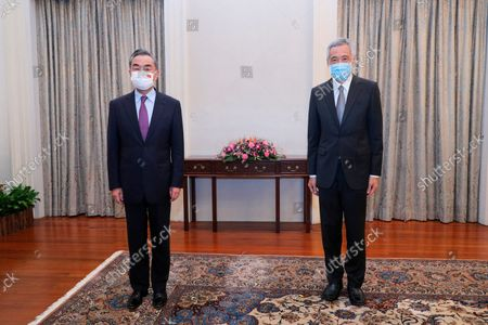 In this image provided by the Singapore Ministry of Communications and Information, Singapore Prime Minister Lee Hsien Loong, right, and Chinese Foreign Minister Wang Yi stand together for a photo at the Istana Presidential Palace in Singapore, . China's top diplomat met in Singapore with the wealthy city-state's prime minister, reaffirming the importance of trade and diplomatic ties between the two countries
