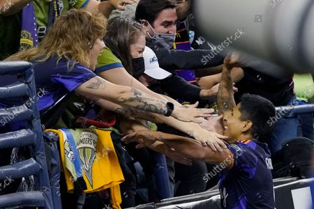 Seattle Sounders forward Raul Ruidiaz, right, celebrates with fans after he scored a goal against Santos Laguna during the second half of a Leagues Cup soccer semifinal, in Seattle. The Sounders won 1-0