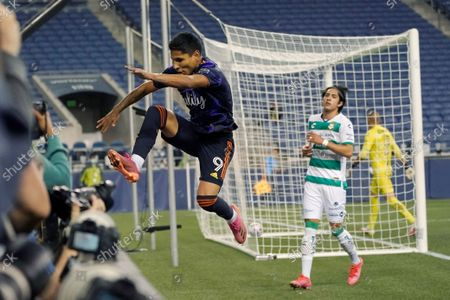 Seattle Sounders forward Raul Ruidiaz (9) leaps over the end line wall as he celebrates after scoring a goal against Santos Laguna during the second half of a Leagues Cup soccer semifinal, in Seattle. The Sounders won 1-0