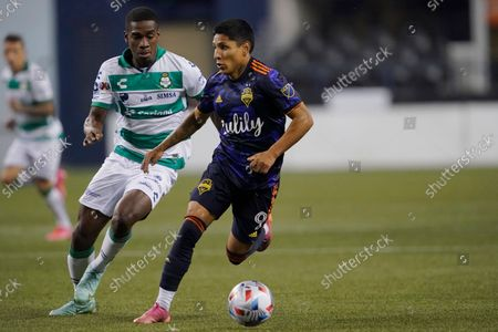 Stock Picture of Seattle Sounders forward Raul Ruidiaz, right, drives away from Santos Laguna defender Felix Torres, left, during the second half of a Leagues Cup soccer semifinal, in Seattle. The Sounders won 1-0