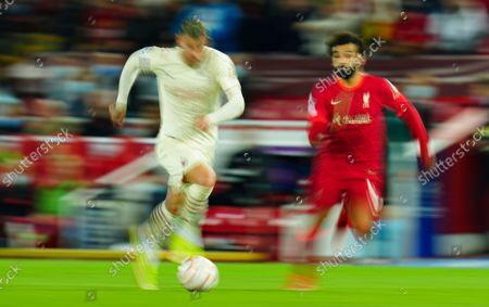 Mohamed Salah of Liverpool tracks back as Théo Hernandez of AC Milan runs upfield