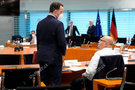 German Health Minister Jens Spahn, left, talks with German Economy Minister Peter Altmaier, right, prior to the weekly cabinet meeting of the German government at the chancellery in Berlin