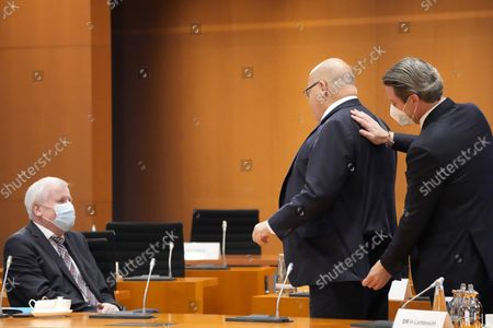 German Transportation Minister Andreas Scheuer, right, helps German Economy Minister, Peter Altmaier, center, with his blazer, as they talk with German Interior Minister Horst Seehofer, left, prior to the weekly cabinet meeting of the German government at the chancellery in Berlin