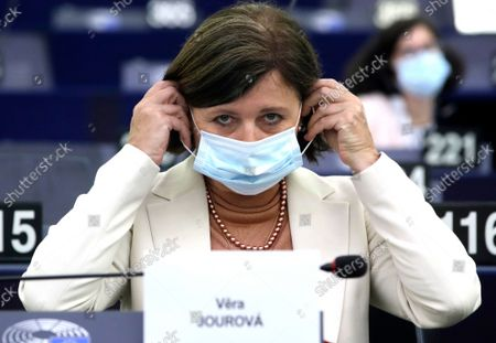 European Commissioner for Values and Transparency Vera Jourova puts on her protective face mask after speaking during a plenary session at the European Parliament in Strasbourg, France