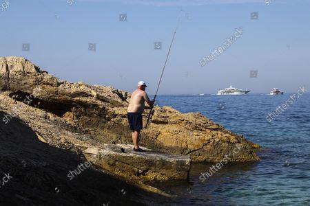 A man is fishing on a rocky beach in Primosten, Croatia on September 14, 2021.