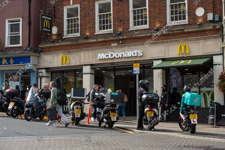 Delivery driver bikes outside McDonald's as many people continue to have fast food delivered to their homes