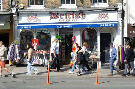 Shoppers pass a tourist shop in Windsor. The number of positive Covid-19 cases in the Royal Borough of Windsor per 100,000 people in the seven days up to and including 10 September compared with the week before are 345, down from 387. Under the latest Government Plan A, unvaccinated people will be encouraged to be jabbed, vaccines will be offered to 12 to 15 year old children and booster jabs are to be rolled out to over 50s