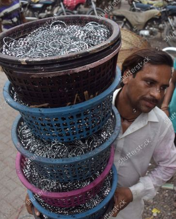 Stock Picture of A Pakistani person works in a bangle factory in Hyderabad, Pakistan, 16 September 2021. The workers use fire to heat and join the bangles manually. They earn 53 US dollars per month working more than 12 hours per day. Colorful bangles are a traditional ornament popular to Asian women including Bangladesh, and India.