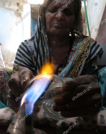 Stock Photo of A Pakistani person works in a bangle factory in Hyderabad, Pakistan, 16 September 2021. The workers use fire to heat and join the bangles manually. They earn 53 US dollars per month working more than 12 hours per day. Colorful bangles are a traditional ornament popular to Asian women including Bangladesh, and India.