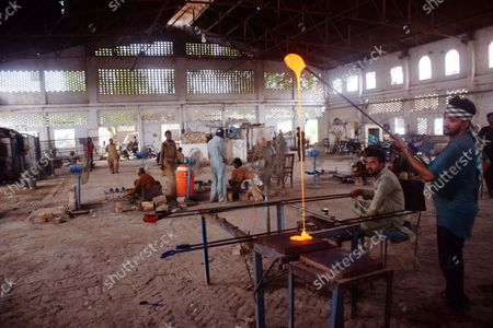 Pakistani laborers work in a bangle factory in Hyderabad, Pakistan, 16 September 2021. The workers use fire to heat and join the bangles manually. They earn 53 US dollars per month working more than 12 hours per day. Colorful bangles are a traditional ornament popular to Asian women including Bangladesh, and India.