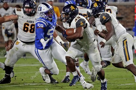 North Carolina A&T running back Bhayshul Tuten (33) looks to evade Duke defensive end Michael Reese (59) during the first half of an NCAA college football game in Durham, N.C
