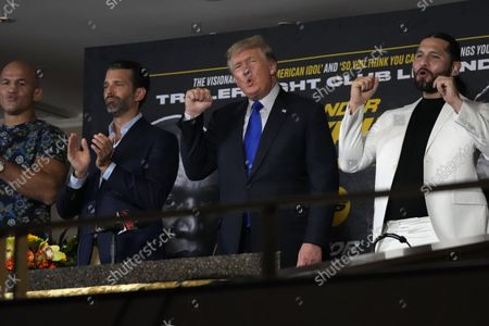"""Former President Donald Trump, center right, chants """"USA, USA"""" along with the crowd, after the U.S. anthem was played at a boxing event where Trump and his son, Donald Trump Jr., center left, were providing commentary, in Hollywood, Fla"""