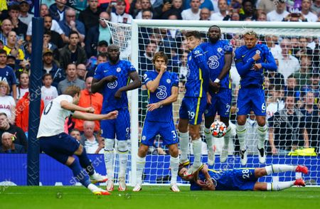 The Chelsea defensive wall jumps as Harry Kane of Tottenham Hotspur takes a free kick