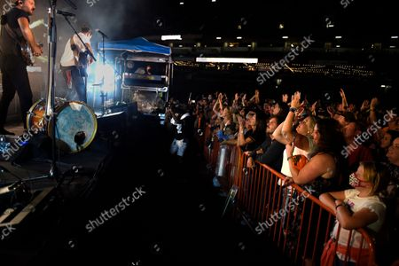 Stock Photo of Fans applauded the folk-rock band, The Avett Brothers, featuring Scott Avett, left, and Seth Avett perform in a post game concert after the Baltimore Orioles and New York Yankees baseball game, in Baltimore
