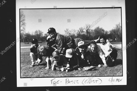 CBS-TV correspondent Bill Geist reliving his experience as a Little League baseball coach as he lies out across the backs of 7 Little Leaguers  incl. his daughter Libby  who are supporting him on their hands & knees at local baseball diamond