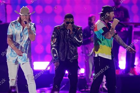 Nelly, center, performs with Brian Kelley, left, and Tyler Hubbard of Florida Georgia Line on the first night of the 2021 iHeartRadio Music Festival, in Las Vegas