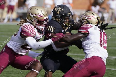 Wake Forest running back Christian Turner, center, is tackled by Florida State defensive back Sidney Williams, left, and defensive back Travis Jay during the first half of an NCAA college football game, in Winston-Salem, N.C