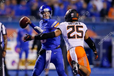 Stock Photo of Boise State quarterback Hank Bachmeier (19) is pressured by Oklahoma State safety Jason Taylor II (25) during the second half of an NCAA college football game, in Boise, Idaho