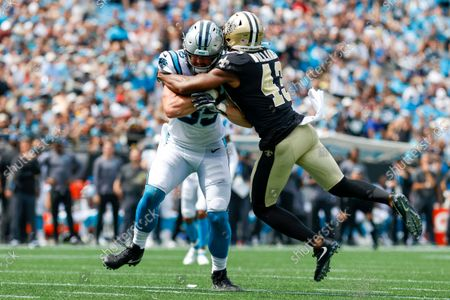 New Orleans Saints free safety Marcus Williams, right, tackles Carolina Panthers tight end Dan Arnold during the first half of an NFL football game, in Charlotte, N.C
