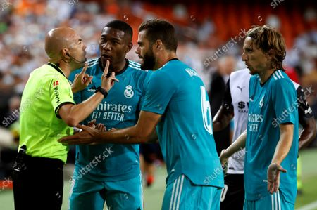 Real Madrid's defenders Nacho Fernandez (2-R) and David Alaba (2-L) and midfielder Luka Modric (R) argue with referee Gonzalez Fuertes (L) during the Spanish LaLiga soccer match between Valencia CF and Real Madrid held at Mestalla stadium in Valencia, eastern Spain, 19 September 2021.