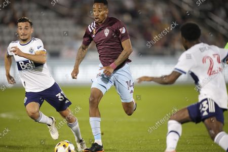 Stock Picture of Colorado Rapids midfielder Mark-Anthony Kaye, center, drives with the ball between Vancouver Whitecaps midfielder Russell Teibert, left, and defender Javain Brown in the first half of an MLS soccer match, in Commerce City, Colo