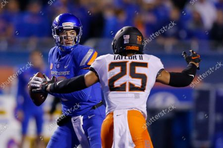 Boise State quarterback Hank Bachmeier (19) looks downfield as Oklahoma State safety Jason Taylor II (25) pressures him during the second half of an NCAA college football game, in Boise, Idaho. Oklahoma State won 21-20