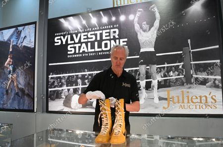 Stock Image of A Julien's Auctions employee poses for photographers with Rocky Balboa boots from Rocky III during a photocall for 'Property From The Life And Career of US actor Sylvester Stallone' at the Mall Galleries in London, Britain 20 September 2021. A collection of over 500 costumes, movie props, and memorabilia from Stallone's most iconic movies will go under the hammer at an auction in Beverley Hills on 05 December 2021.