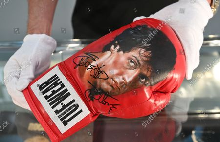 A Julien's Auctions employee poses for photographers with a signed Rocky boxing glove during a photocall for 'Property From The Life And Career of US actor Sylvester Stallone' at the Mall Galleries in London, Britain 20 September 2021. A collection of over 500 costumes, movie props, and memorabilia from Stallone's most iconic movies will go under the hammer at an auction in Beverley Hills on 05 December 2021.