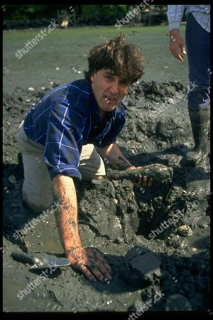 Stock Image of Geoduck Clams feature. Portrait of clamdigger David Guterson holding mucky clam.