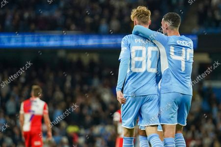 Manchester City's Cole Palmer is congratulated by teammate Phil Foden, right, after scoring his team's fifth goal during the English League Cup third round soccer match between Manchester City and Wycombe Wanderers at Etihad Stadium, in Manchester England