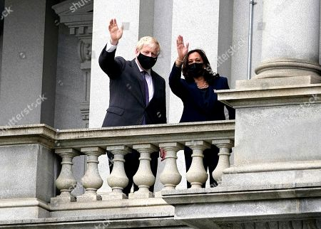 Vice President Kamala Harris waves with British Prime Minister Boris Johnson, in Washington, as they take a walk on her office balcony on the White House complex
