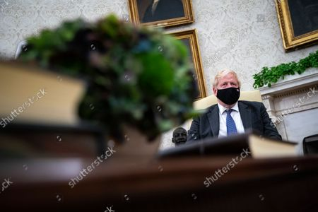 Prime Minister Boris Johnson of the United Kingdom listens during a meeting with United States President Joe Biden in the Oval Office of the White House in Washington, DC, on Tuesday, September 21, 2021.
