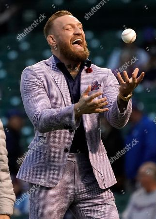 Fighter Conor McGregor laughs as he tosses the ball in the air after throwing out a ceremonial first pitch before a baseball game between the Chicago Cubs and the Minnesota Twins, in Chicago