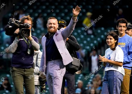 Fighter Conor McGregor waves to fans before throwing out a ceremonial first pitch before a baseball game between the Chicago Cubs and the Minnesota Twins, in Chicago