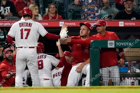 Los Angeles Angels' Shohei Ohtani (17) is met in the dugout by Mike Trout, center, and bench coach Mike Gallego, right, during the sixth inning of a baseball game against the Houston Astros, in Anaheim, Calif