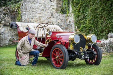 Stock Image of National Motor Museum's Ben Wanklyn cleans Mr Toad's car in the museum grounds.  Mr Toad's car from Wind in the Willows has gone on display after a painstaking restoration following years of neglect.  The vehicle was made for the 1996 film adaptation of Kenneth Grahame's classic 1908 children's book starring Terry Jones as the obsessive amphibian.  The car, which appears to be from the Edwardian era, was actually built in 1995 at Shepperton Studios for the film.  Following the film's release, it was transported to America, where it spent many years hanging from the ceiling of a Florida restaurant.  It was brought back to Britain last year in a dilapidated state and has been restored at the National Motor Museum workshop in Beaulieu, Hants, where visitors can see it driven around the grounds.