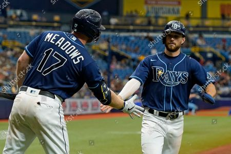 Tampa Bay Rays' Brandon Lowe, right, celebrates with Austin Meadows after scoring on a sacrifice fly by Yandy Diaz off Toronto Blue Jays starting pitcher Ross Stripling during the third inning of a baseball game, in St. Petersburg, Fla