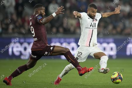 Metz's Habib Maiga, left, and PSG's Rafinha battle for the ball during the French League One soccer match between FC Metz and Paris Saint-Germain at Saint Symphorien stadium, in Metz, eastern France