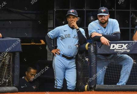 Toronto Blue Jays manager Charlie Montoyo (L) and coach John Schneider (R) watch from the dugout during the first  inning against the Tampa Bay Rays at Tropicana Field in St. Petersburg, Florida on Wednesday, September 22, 2021.