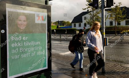"""People walk past an election poster from the Left Green Party, showing Prime Minister Katrin Jakobsdottir and saying """"It isn't coincidence that the City Lane was launched"""" in Reykjavik, Iceland, . Climate change is top of the agenda when voters in Iceland head to the polls for general elections on Saturday, following an exceptionally warm summer and an election campaign defined by a wide-reaching debate on global warming. Polls suggest Prime Minister Katrin Jakobsdottir's Left Green Party could face a poor outcome, ending the current coalition"""
