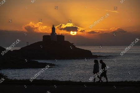 People out walking at Bracelet Bay as the sun rise above the Mumbles Lighthouse on the Gower Peninsula near Swansea this morning.