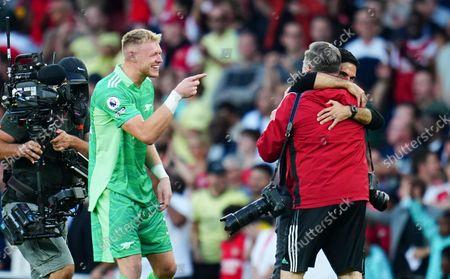 Arsenal goalkeeper Aaron Ramsdale points at Club Photographer Stuart MacFarlane as he hugs manager Mikel Arteta at full time