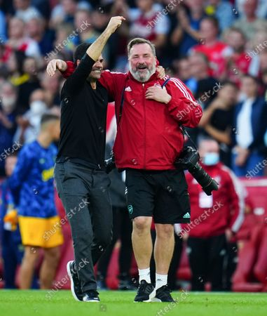 Arsenal manager Mikel Arteta celebrates at full time with club photographer Stuart MacFarlane