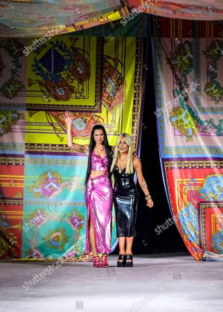 Dua Lipa, left, and Donatella Versace acknowledge applause at the conclusion of the Versace Spring Summer 2022 collection during Milan Fashion Week, in Milan, Italy