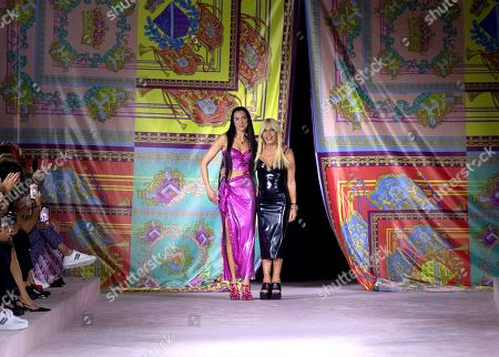 British singer-songwriter Dua Lipa (L) and Italian designer Donatella Versace (R) appear on the catwalk at the end of the Versace show during the 'Milano Moda Donna' Spring/Summer 2022 Milan Women's Fashion Week in Milan, Italy, 24 September 2021. The Milan Women's Fashion Week runs from 21 to 27 September 2021.